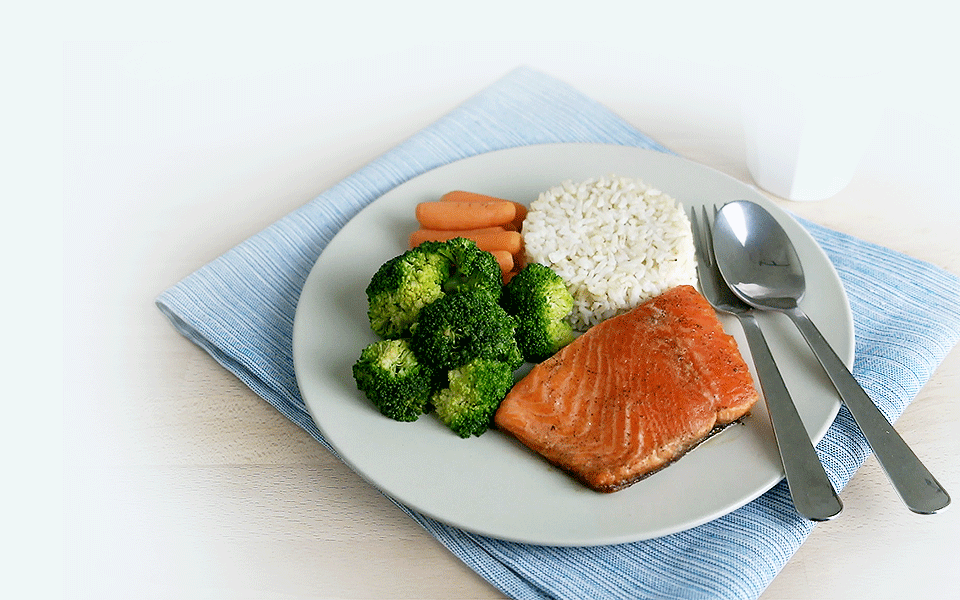 Healthy meal of baked salmon with broccoli and carrots and rice""